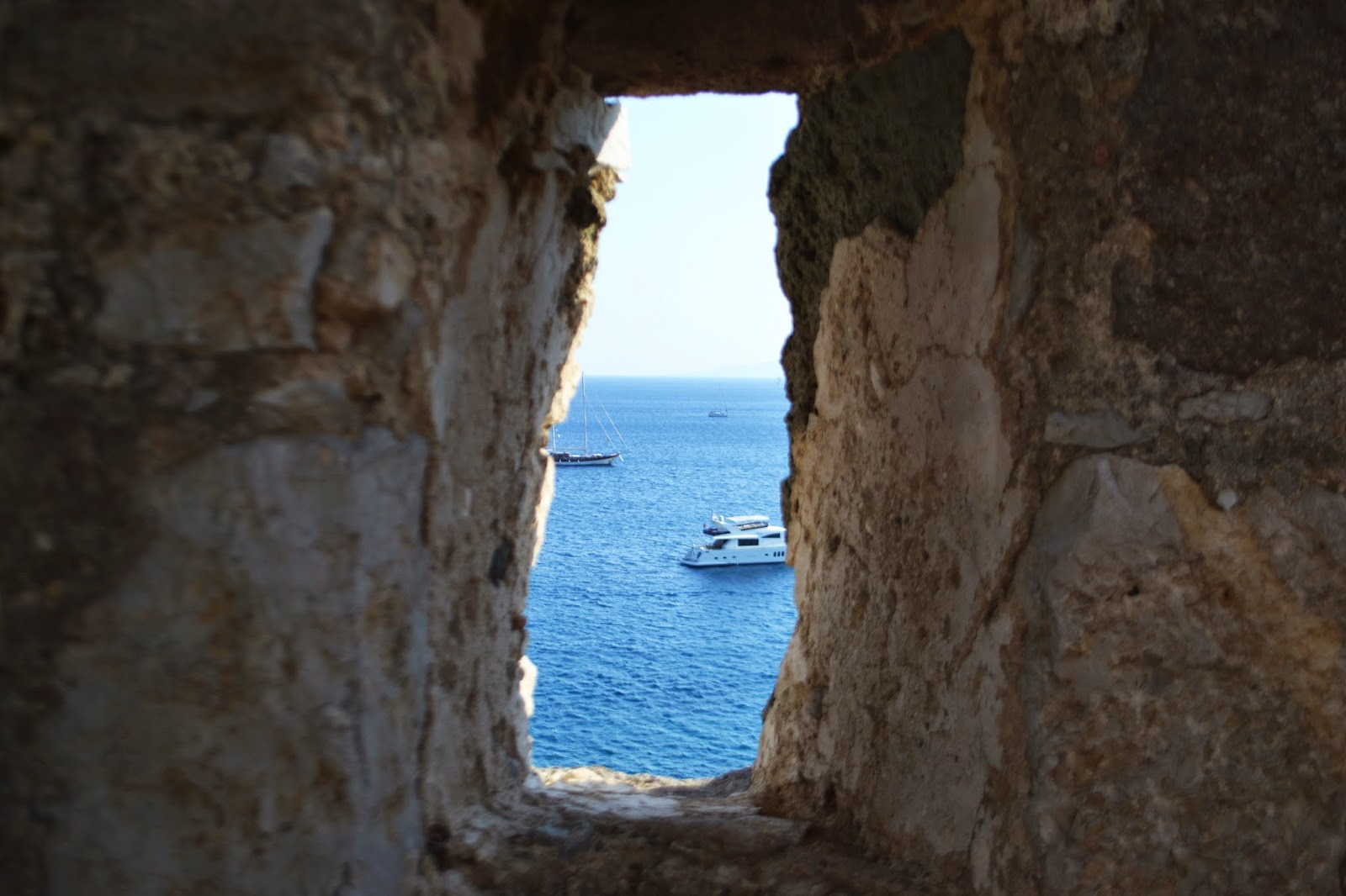 a small hole on the wall at Bodrum castle looks out over the sea where boats can be seen