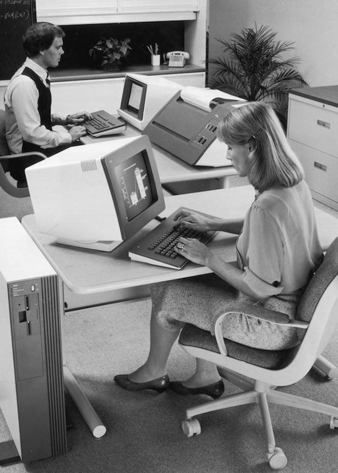 A woman uses a personal computer at the NCR research and development facility in West Columbia, South Carolina. She wears a blouse with rolled sleeves and a formal knee- or calf-length tweed skirt, with court shoes. Her hair is shoulder-length, held away from her face by a slide. 1982.