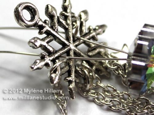 Wire prongs inserted through the arms of a silver snowflake charm