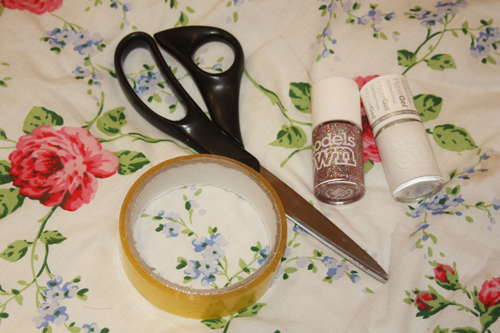 from left to right; cellotape, scissors, pink glittery nail polish (models own northern lights), and white nail polish (models own hypergel in white light), all lying on a floral duvet