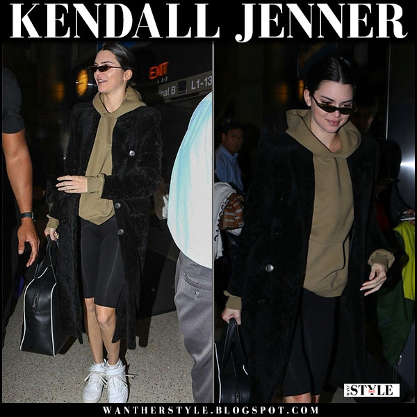 Kendall Jenner in black balenciaga coat, black bike shorts and white sneakers adidas airport fashion march 17