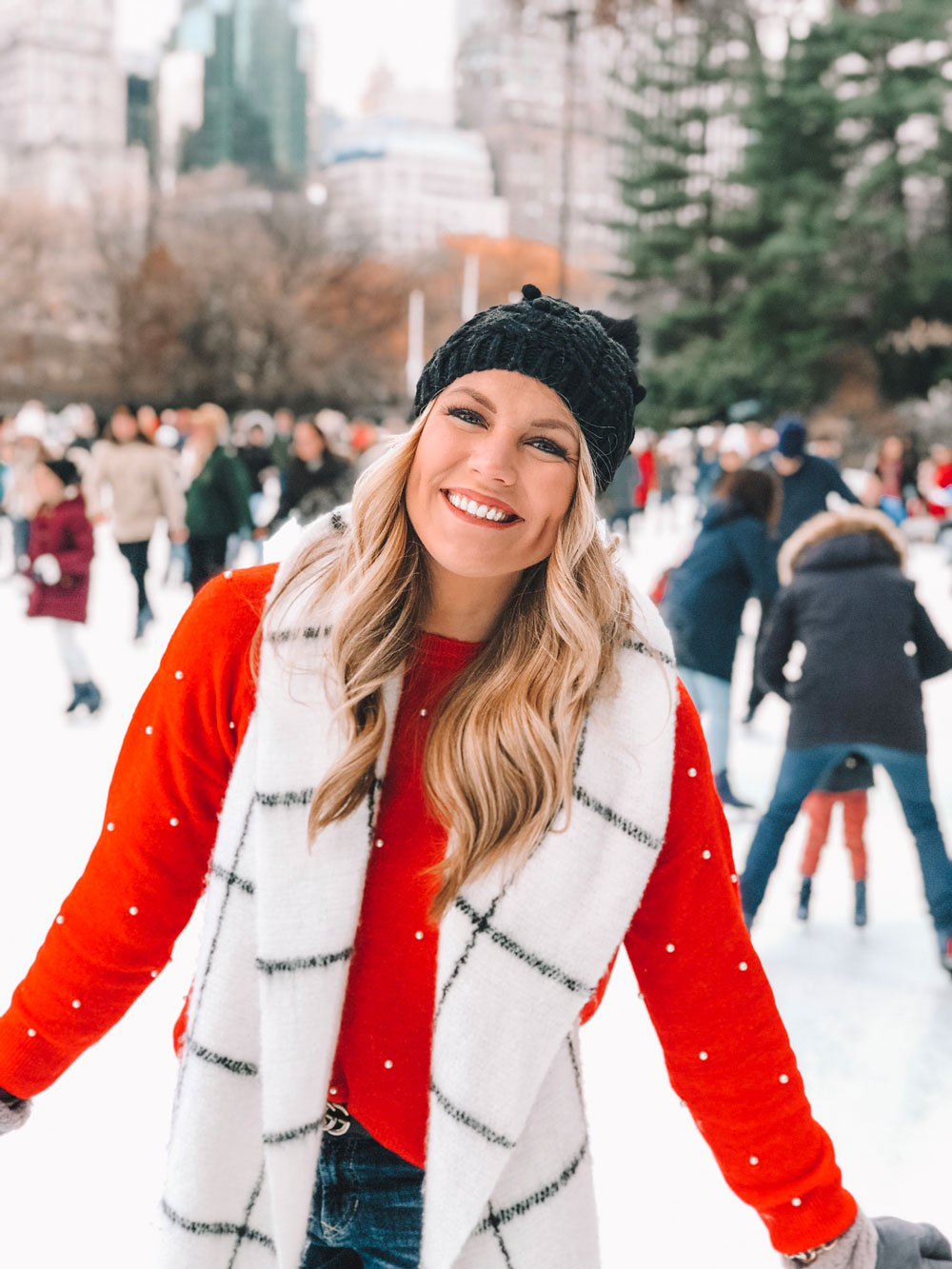 Amanda Martin of Amanda's OK Blog ice skates at the Wollman Rink wearing a red pearl sweater from H&M