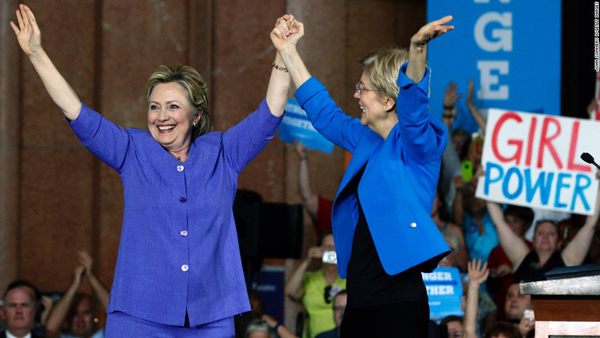image of Clinton and Warren grasping hands onstage, wearing matching blue jackets