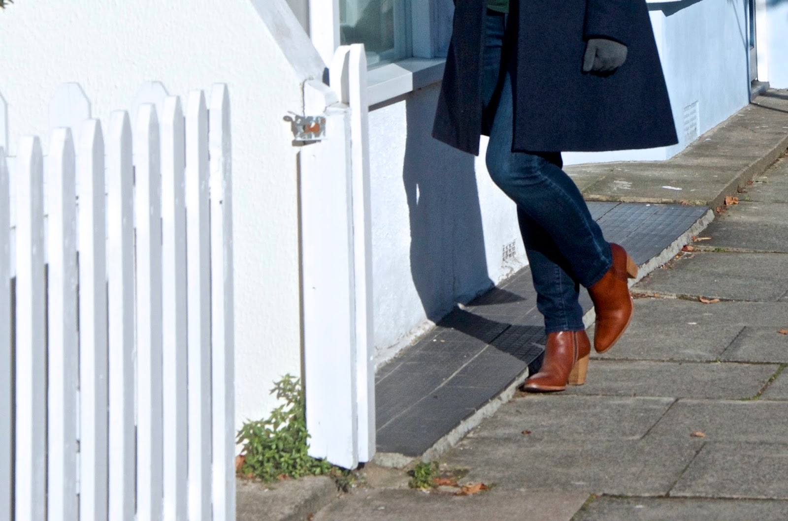 Navy coat, grey gloves, jeans and brown boots with white picket fence