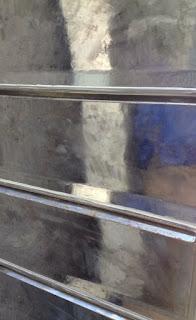 Clapet de meuble en métal en cours de ponçage