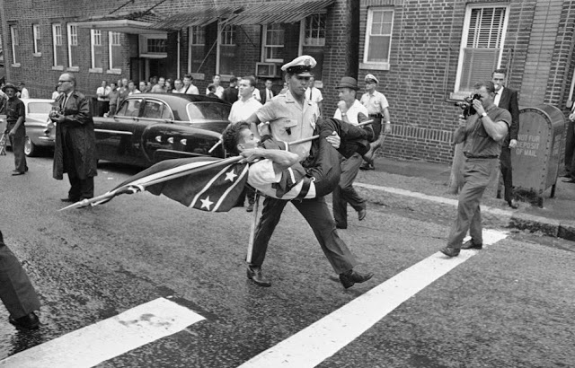 Sept. 4, 1963, a police officer removes a demonstrator holding a Confederate flag after a group of demonstrators protested enrollment of two African-Americans at Ramsay High School in Birmingham, Alabama.