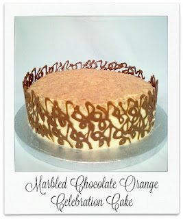 This cake is a lot easier to make than it may appear.  The chocolate orange marbled sponge cake is sandwiched with orange curd before being coated with a white chocolate ganache frosting.  Chocolate orange segments were used for the collar work.