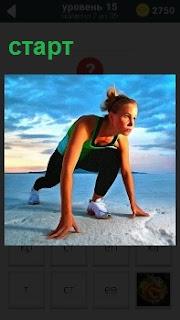 Девушка приняла стойку на земле для быстрого старта в спортивной форме на фоне облаков