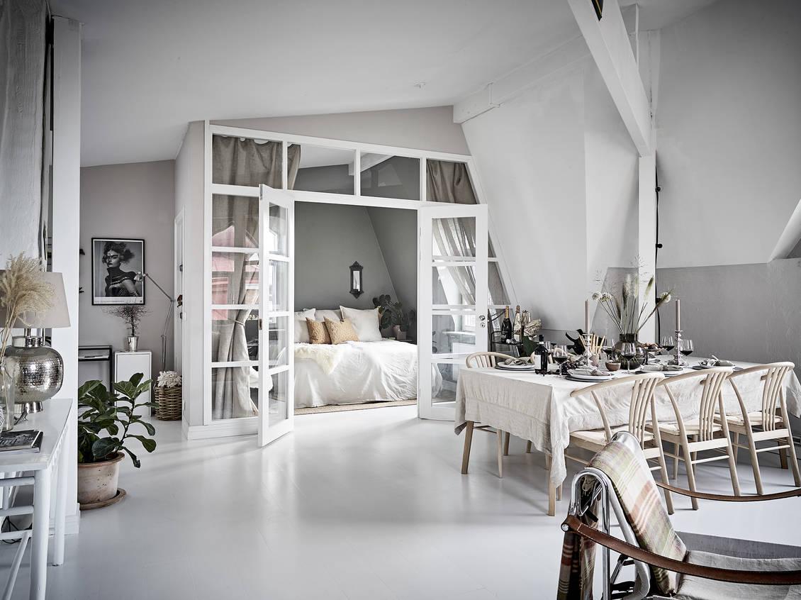Dormitor închis cu pereți de sticlă în amenajarea unei mansarde spațioase din Suedia