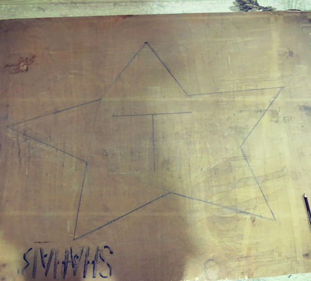 drawn star on a board with pencil