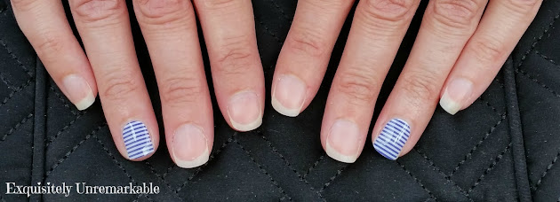 Eight naked fingernails and two with blue and white striped nail wraps