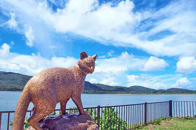 Bronze statue of Yamaneko with river, sky and mountain background