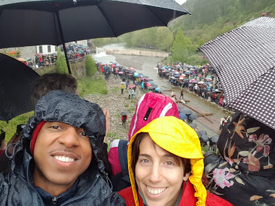 Lots of people standing in the rain watching almadias go down the river