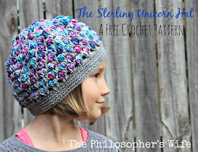 A girl is wearing a crocheted hat looking off to the side.