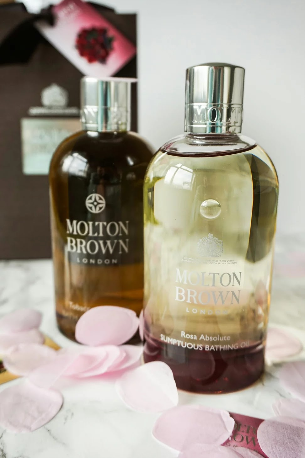 Molton Brown rose absolute and tobacco absolute bottles covered in confetti