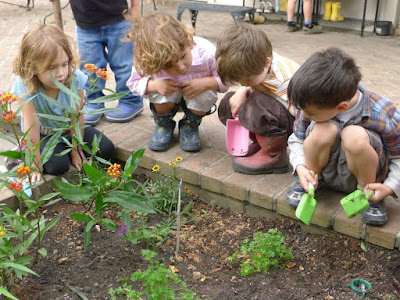 Four young children with plastic gardening tools crouched around a garden,