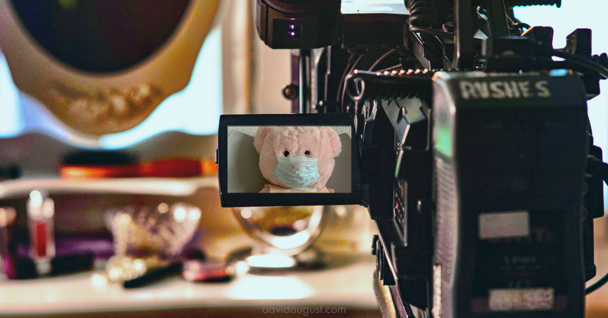 picture of a video camera on set with a pink teddy bear wearing a face mask on the view finder screen