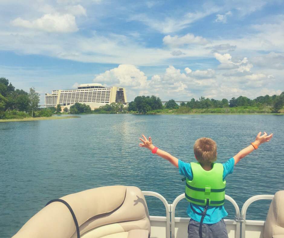 A young boy stands on a boat with his hands in the air as he looks at Contemporary Resort in Walt Disney World.