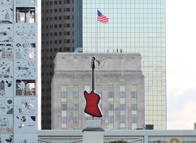 Roof-top red guitar at Hardrock Cafe with top of City Hall in background with US Flag