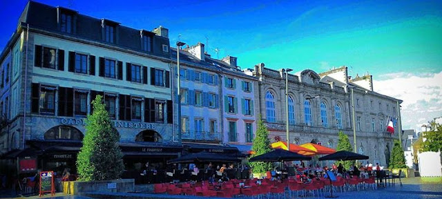 café du finistère quimper with tourists sitting on red chairs