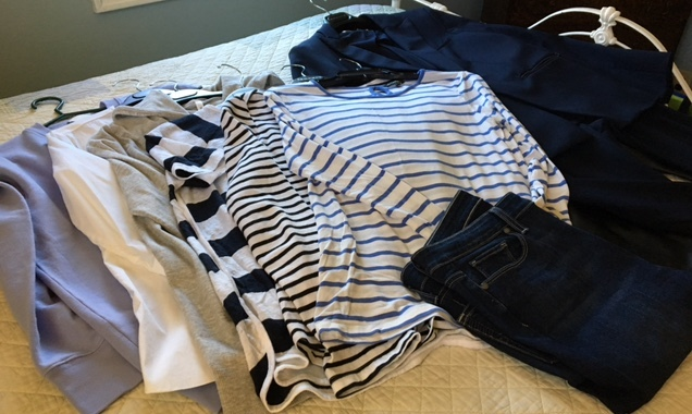tee shirts, jackets and jeans lying on a bed