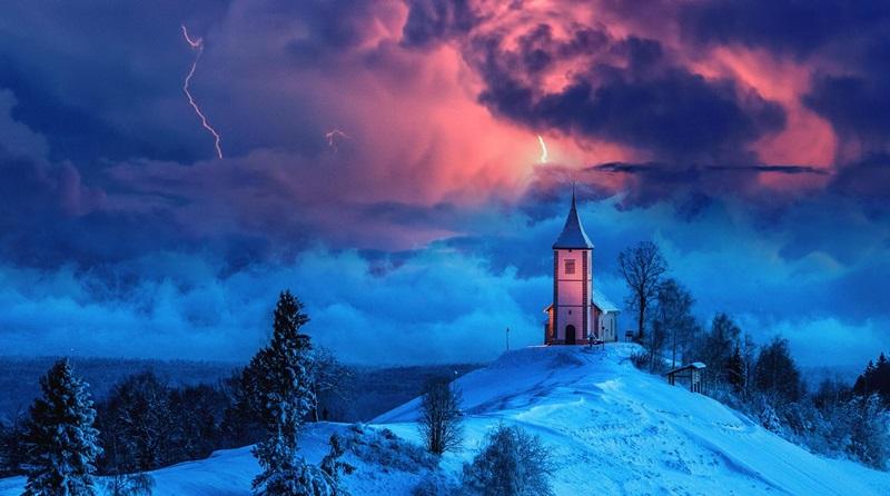A igreja sendo atacada por nuvens negras e raios