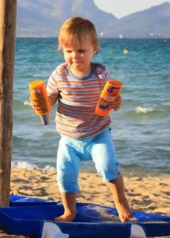 Kind auf Liege am Strand mit Sonnencreme in der Hand