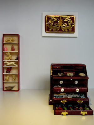 Modern miniature gallery space displaying a writing desk and shelves full of pieces on display, and a gold and red chinese piece on the wall.