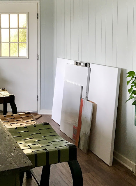 Blank canvasses leaning against bare wall