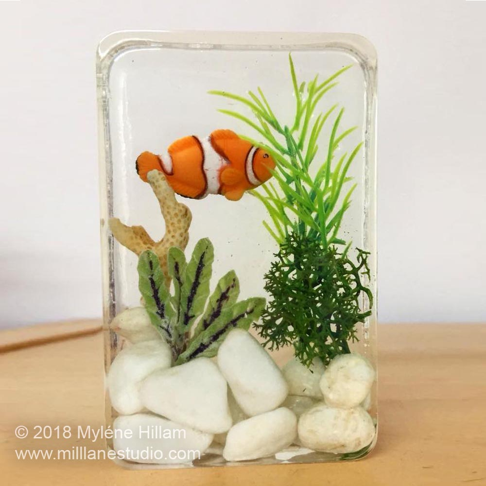 Create a faux mini aquarium with clear casting polyester resin complete with a mini fish, seaweed and coral.