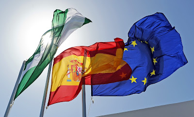 Pic of 3 flags flying at top of flagpoles in sunshine: Andalusian, Spanish and EU