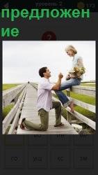 мужчина делает предложение женщине на коленях