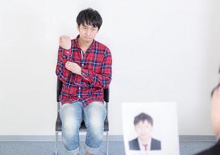 用務員の面接に臨む男性の画像を表示しています。