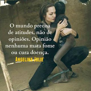 Foto. Angelina Jolie em um pátio de chão de areia, está agachada com o joelho direito apoiado no chão e sobre a coxa da outra perna dobrada e aérea, apoia um garoto magérrimo de pele negra com aspecto ressecado e sujo, o corpo nu parcialmente coberto por camiseta escura, bem maior que ele. Com a cabeça voltada para trás ele abraça a protetora que retribui ternamente espalmando a mão direita abaixo do ombro esquerdo do menino e o braço esquerdo enlaça-o e a mão em concha circunda a frágil cintura. O garoto tem o tornozelo esquerdo amarrado por um tecido azul retorcido, preso a uma corda fortemente estirada em uma estaca de pau. Angelina é uma mulher de pele alva, magra, rosto oval, cabelos castanhos escuros lisos e compridos presos para trás por uma fina tiara preta, sobrancelhas curtas, olhos fechados, nariz médio levemente arrebitado e lábios grossos; ela usa um macacão e botinas pretos. Ao fundo, um muro com reboco rachado e em uma parte à direita, no alto, quebrado.  Sobreposto à foto escrito em letras brancas, lê-se: O mundo precisa de atitudes, não de opiniões. Opinião nenhuma mata fome ou cura doença. Angelina Jolie.