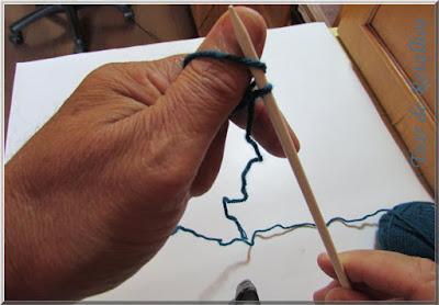 Foto mostrando a agulha de tricô introduzida na alça de fio que está envolvendo o polegar para a montagem simples dos pontos da base.