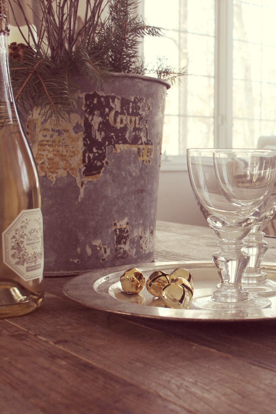 White wine, goblets, and gold bells on rustic table - Hello Lovely Studio
