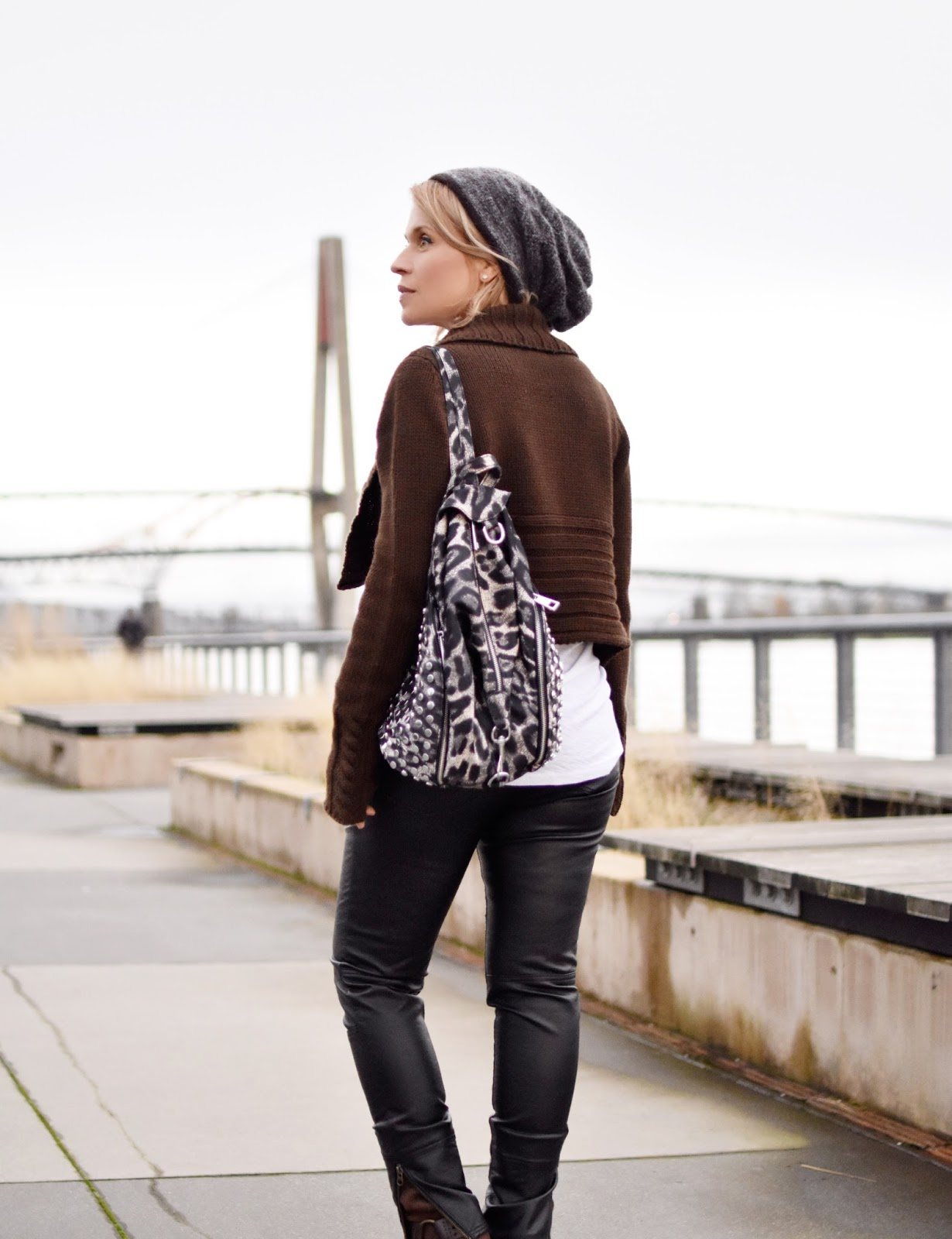 "Monika Faulkner outfit inspiration - styling a slouchy white tee, vegan leather jeans, cropped ""moto"" cardigan, mohair beanie, and leopard-print backpack"