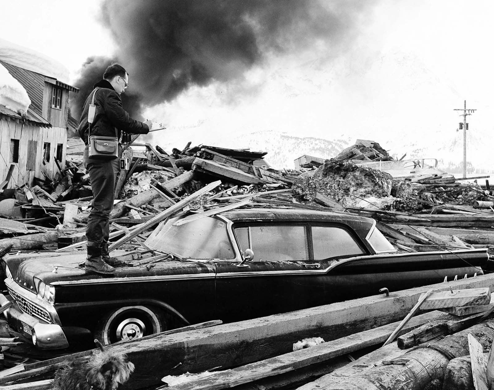 A photographer looks over wreckage as smoke rises in the background from burning oil storage tanks in Valdez, Alaska, on March 29, 1964, two days after the earthquake struck.