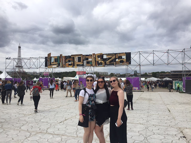 Three girls stood in front of Lollapalooza sign