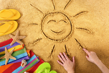 Smiling sunshine drawn in the sand and surrounded by towels, shells and starfish