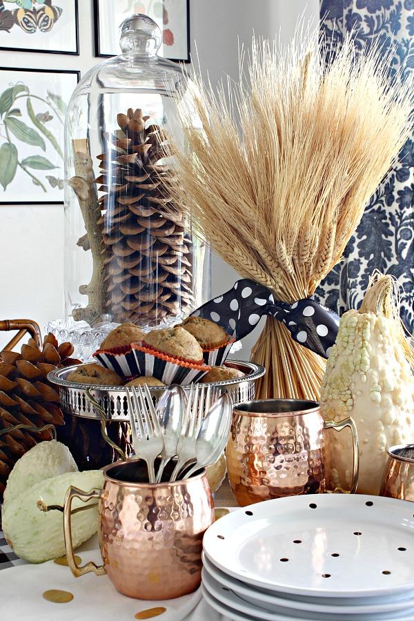 copper mugs, standing wheat bundle, polka dot plates, sugar pine cones, fall decor
