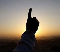 Gün batarken şehadet parmağının gökyüzüne kaldırmış birisi
