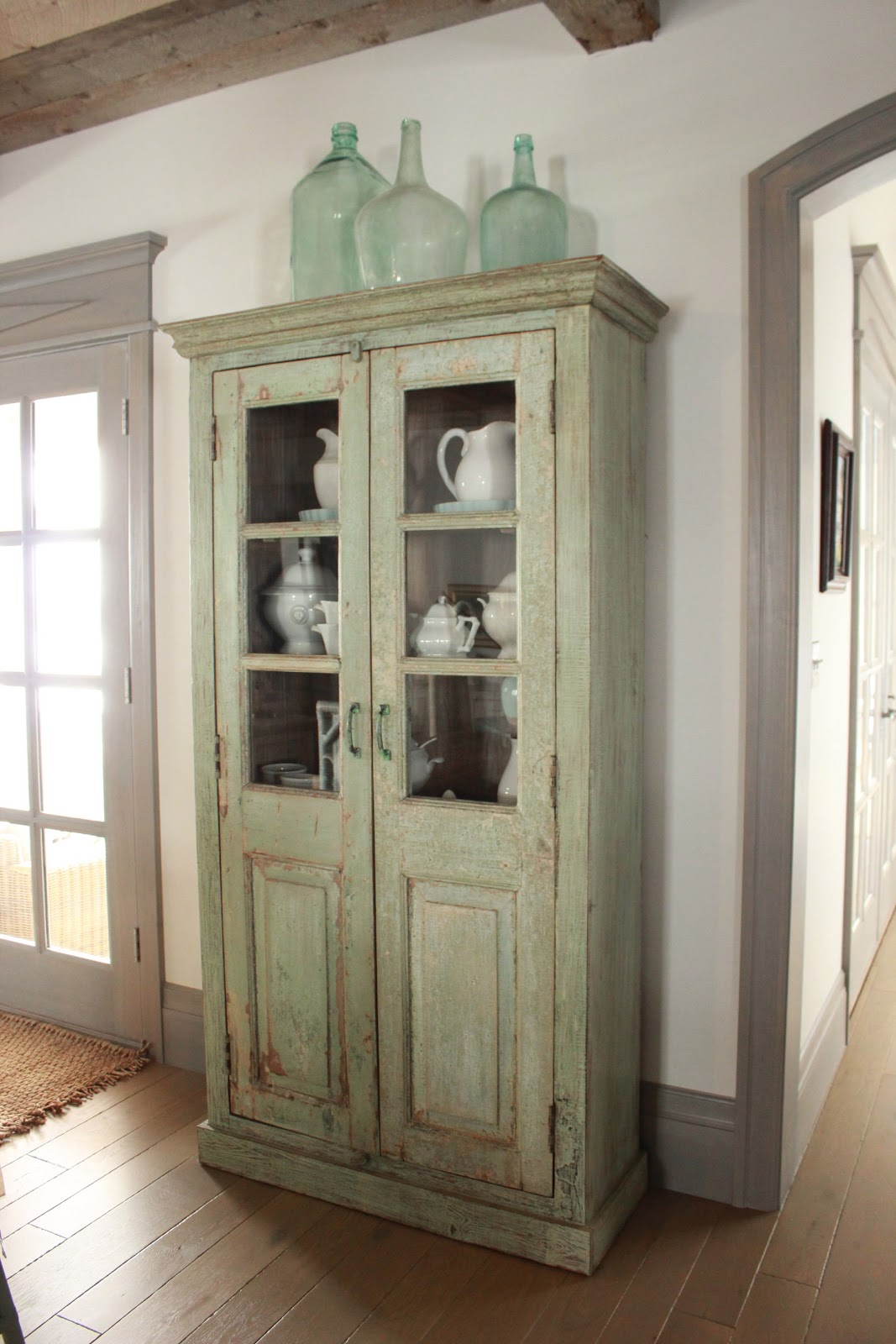 Magnificent Gustavian French weathered green cabinet in stone cottage with rustic interiors, reclaimed wood ceilings, blue-grey, green, and collected European antiques. Designed by Desiree Ashworth. Find ideas for grey, blue, and green paint colors.