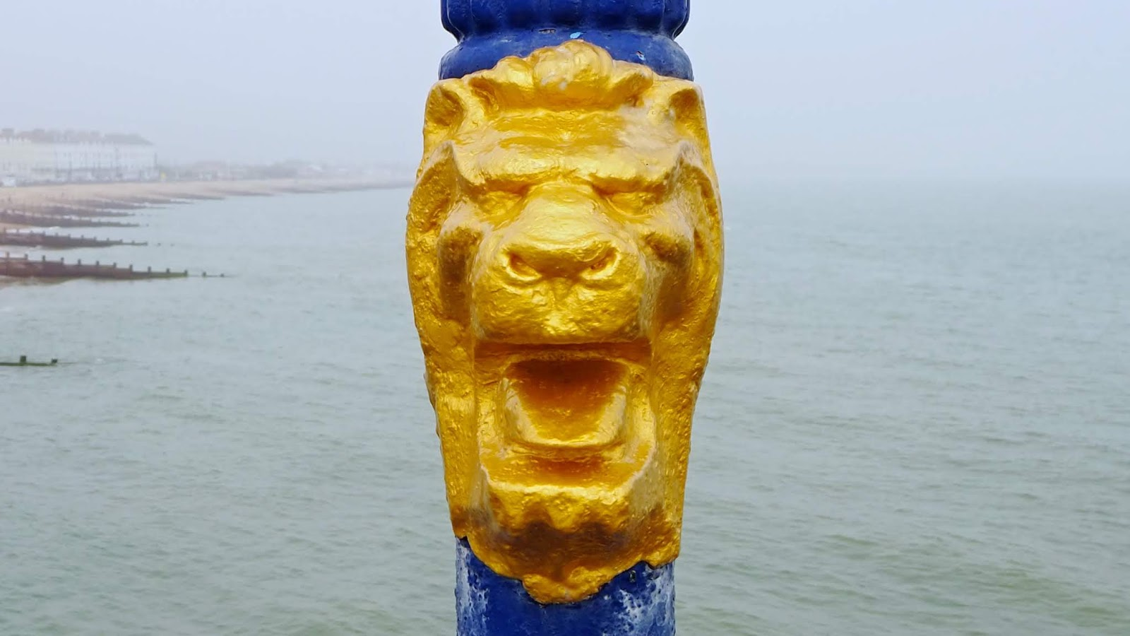 golden lions head on pier