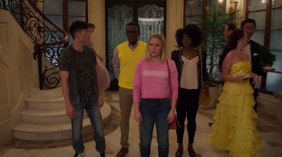 Jason, Chidi, Eleanor, and Simone are all wearing regular street clothes. They're standing in a massive foyer with marble floors and an ornately decorated staircase. Next to them, a man in a tuxedo and a woman wearing a floor-length gown are walking into the party.