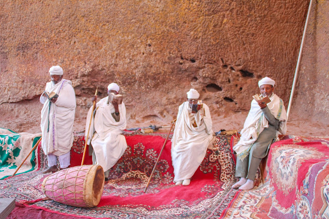 four men in traditional white cotton shawls praying in front of a church
