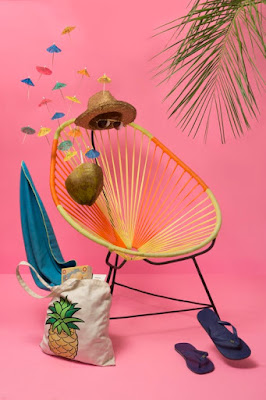 Colorful tropical scene with sunglasses, straw hat, chair and sandals and pink background wall, Guadalajara