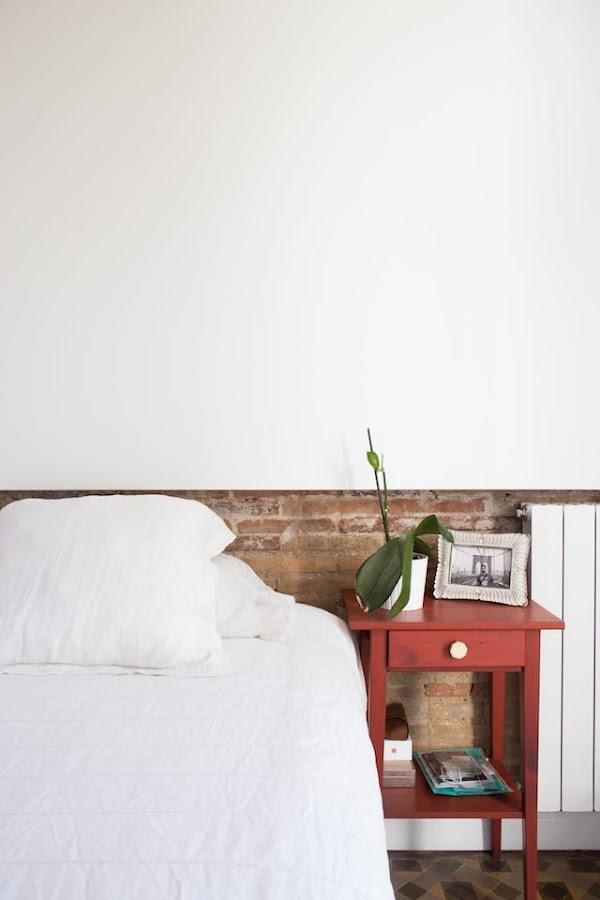 dormitorio con media pared de mampostería y suelos hidráulicos.