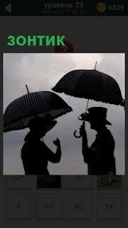 темные силуэты женщины в шляпке и мужчины в головном уборе под зонтиками
