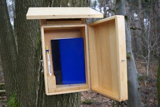 Eine kleine, blaue Kladde steht hochkant in einerArt Vogelhäuschen. Rechts neben der Kladde steckt ein Kugelschreiber